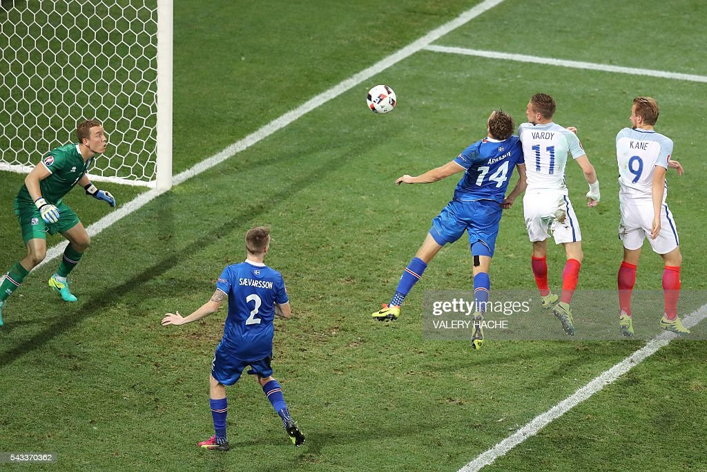Iceland's defender Kari Arnason (C) vies for the ball with England's forward Jamie Vardy and England's forward Harry Kane during the Euro 2016 round of 16 football match between England and Iceland at the Allianz Riviera stadium in Nice on June 27, 2016. Iceland won the match 1-2. / AFP / Valery HACHE