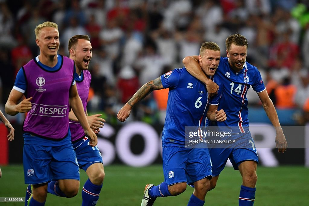 Iceland's defender Ragnar Sigurdsson (2R) and Iceland's defender Kari Arnason (R) celebrate their team's win after the Euro 2016 round of 16 football match between England and Iceland at the Allianz Riviera stadium in Nice on June 27, 2016. Iceland won the match 1-2. / AFP / BERTRAND