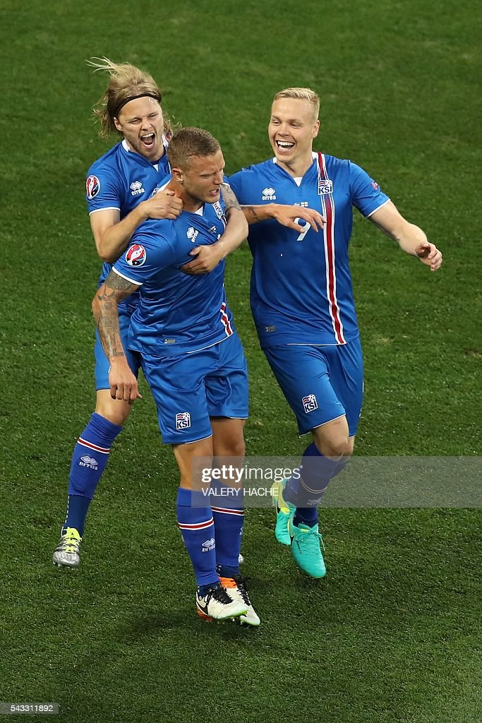 Iceland's defender Ragnar Sigurdsson (C) celebrates scoring a goal with Iceland's midfielder Birkir Bjarnason and Iceland's forward Kolbeinn Sigthorsson during the Euro 2016 round of 16 football match between England and Iceland at the Allianz Riviera stadium in Nice on June 27, 2016. / AFP / Valery HACHE