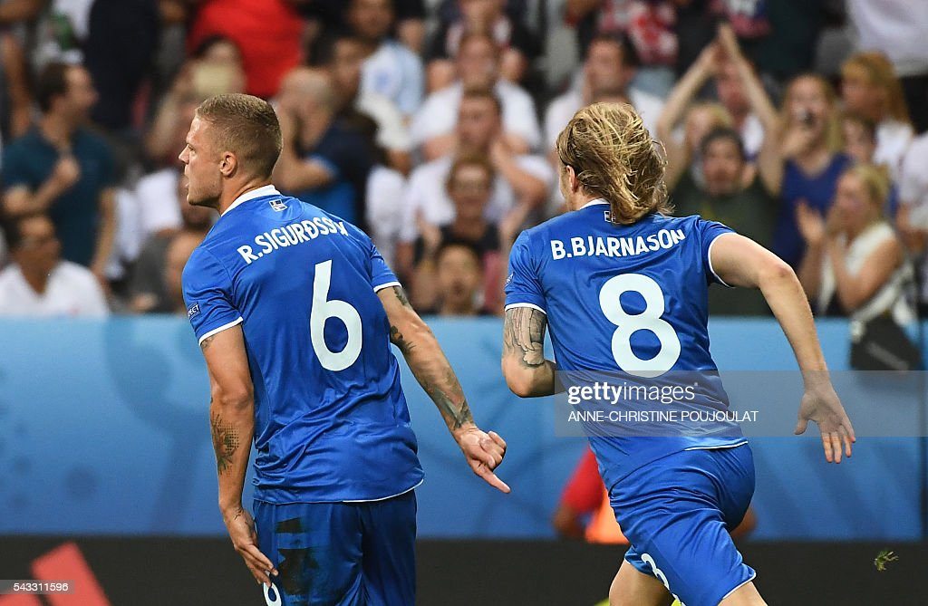 Iceland's defender Ragnar Sigurdsson (L) celebrates with Iceland's midfielder Birkir Bjarnason after scoring the 1-1 during Euro 2016 round of 16 football match between England and Iceland at the Allianz Riviera stadium in Nice on June 27, 2016. / AFP / ANNE