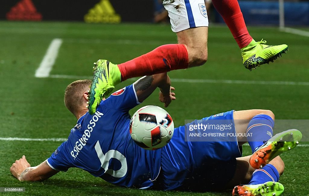 Iceland's defender Ragnar Sigurdsson falls on the pitch as he vies with England's forward Jamie Vardy during Euro 2016 round of 16 football match between England and Iceland at the Allianz Riviera stadium in Nice on June 27, 2016. / AFP / ANNE