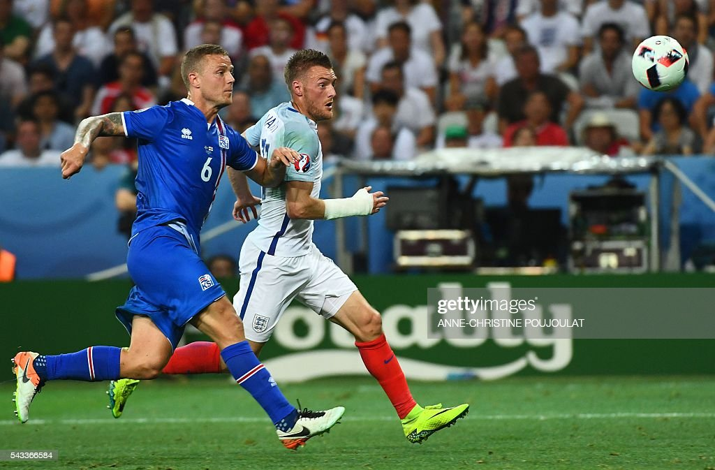 Iceland's defender Ragnar Sigurdsson (L) vies for the ball with England's forward Jamie Vardy during Euro 2016 round of 16 football match between England and Iceland at the Allianz Riviera stadium in Nice on June 27, 2016. / AFP / ANNE