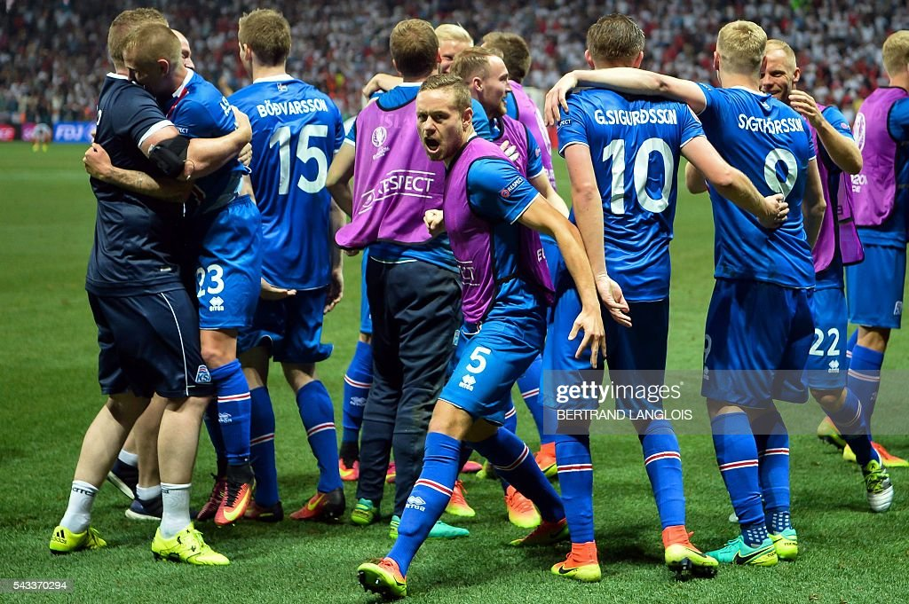 Iceland's players celebrate their team's win with supporters after the Euro 2016 round of 16 football match between England and Iceland at the Allianz Riviera stadium in Nice on June 27, 2016. Iceland won the match 1-2. / AFP / BERTRAND