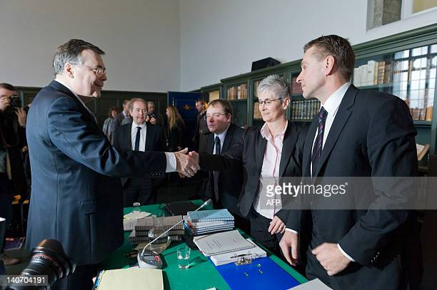 Iceland's exprime minister Geir Haarde shakes hands with Sigridur Fridjonsdottir Parliament prosecutor with her assistant Helgi Magnœs Gunnarsson in...
