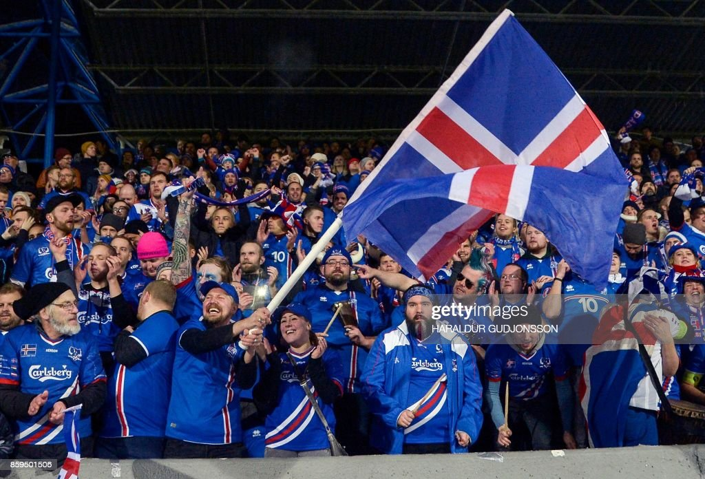 TOPSHOT - Iceland's fans celebrates at the FIFA World Cup 2018 qualification football match between Iceland and Kosovo in Reykjavik, Iceland on October 9, 2017. Iceland qualified for the FIFA World Cup 2018 as smallest country ever after beating Kosovo 2-0 at home in Reykjavik. / AFP PHOTO / Haraldur Gudjonsson / ALTERNATIVE