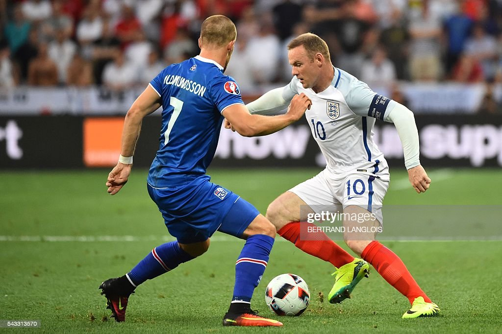 Iceland's forward Johann Berg Gudmundsson (L) and England's forward Wayne Rooney vie for the ball during the Euro 2016 round of 16 football match between England and Iceland at the Allianz Riviera stadium in Nice on June 27, 2016. / AFP / BERTRAND