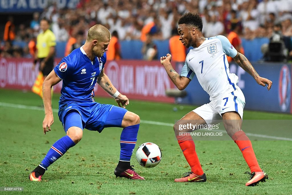 Iceland's forward Johann Berg Gudmundsson (L) and England's midfielder Raheem Sterling vie for the ball during the Euro 2016 round of 16 football match between England and Iceland at the Allianz Riviera stadium in Nice on June 27, 2016. / AFP / BERTRAND