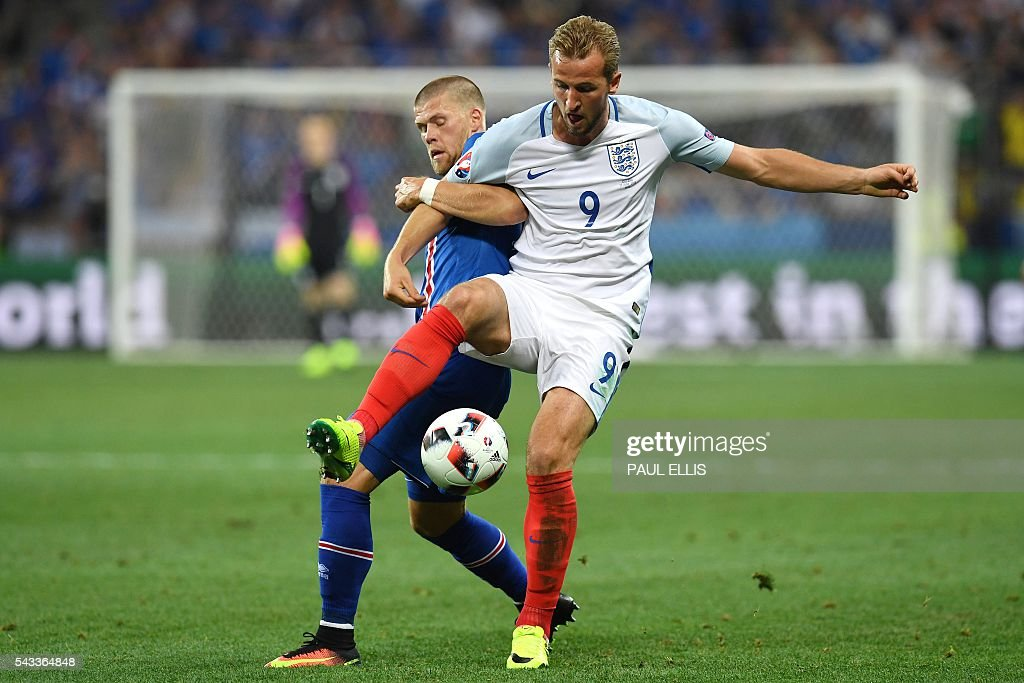 Iceland's forward Johann Berg Gudmundsson (L) vies for the ball against England's forward Harry Kane during Euro 2016 round of 16 football match between England and Iceland at the Allianz Riviera stadium in Nice on June 27, 2016. / AFP / PAUL