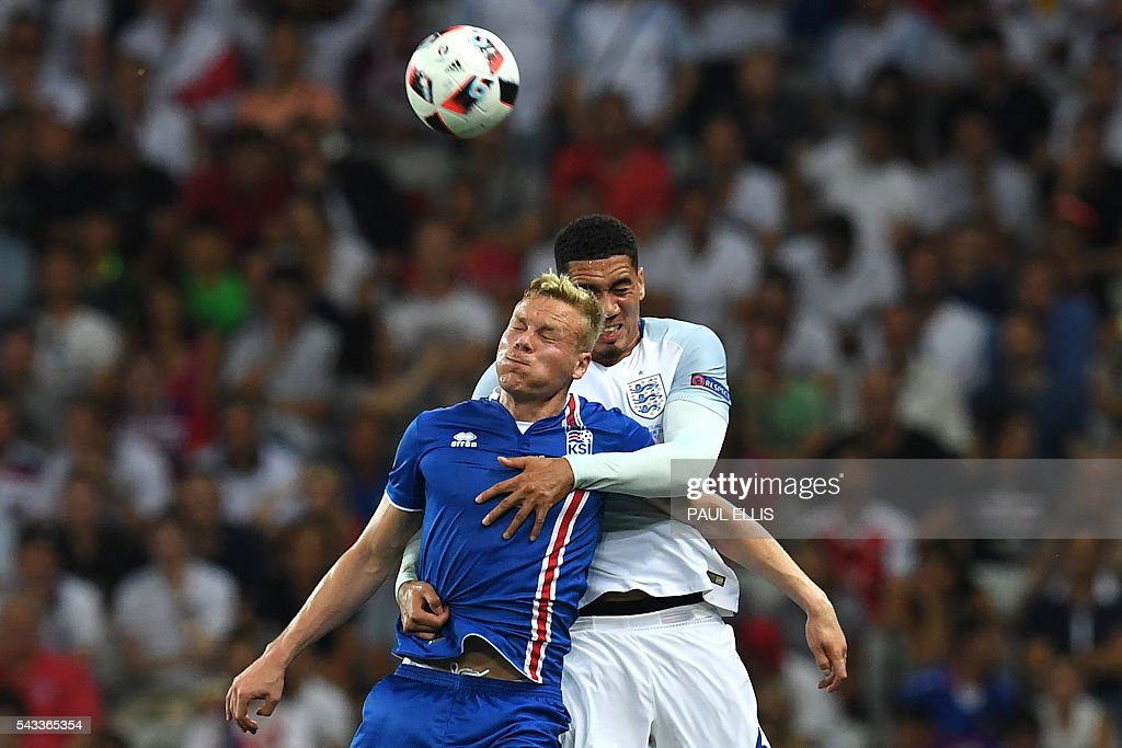 Iceland's forward Kolbeinn Sigthorsson (L) vies for the ball against England's defender Chris Smalling during Euro 2016 round of 16 football match between England and Iceland at the Allianz Riviera stadium in Nice on June 27, 2016. / AFP / PAUL