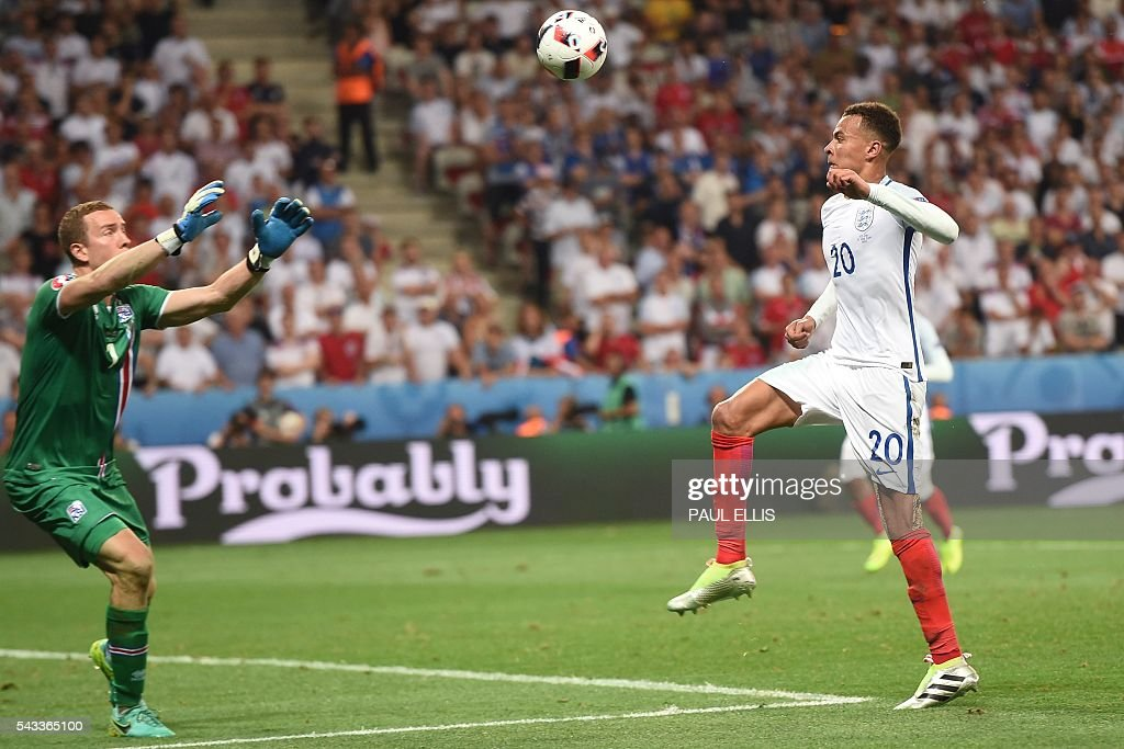 Iceland's goalkeeper Hannes Thor Halldorsson (L) eyes the ball with England's midfielder Dele Alli during Euro 2016 round of 16 football match between England and Iceland at the Allianz Riviera stadium in Nice on June 27, 2016. / AFP / PAUL