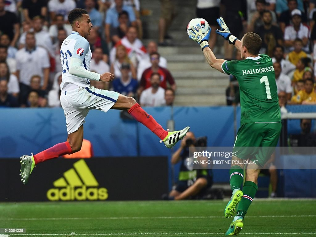 Iceland's goalkeeper Hannes Thor Halldorsson (R) saves the ball in front of England's midfielder Dele Alli during Euro 2016 round of 16 football match between England and Iceland at the Allianz Riviera stadium in Nice on June 27, 2016. / AFP / ANNE