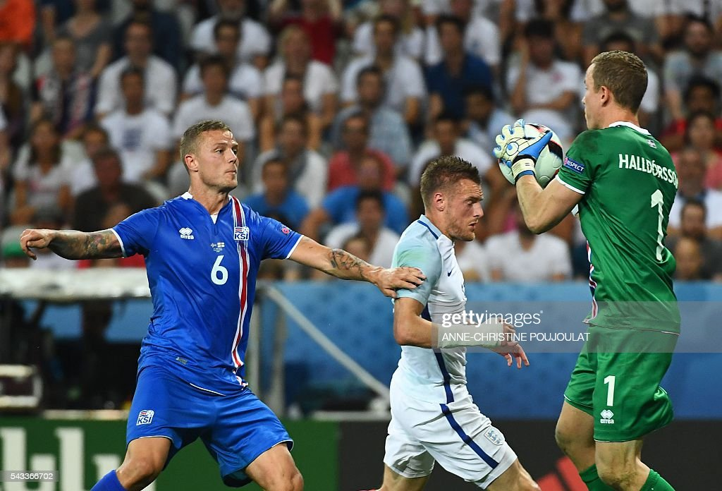 Iceland's goalkeeper Hannes Thor Halldorsson (R) saves the ball in front of Iceland's defender Ragnar Sigurdsson (L) and England's forward Jamie Vardy during Euro 2016 round of 16 football match between England and Iceland at the Allianz Riviera stadium in Nice on June 27, 2016. / AFP / ANNE