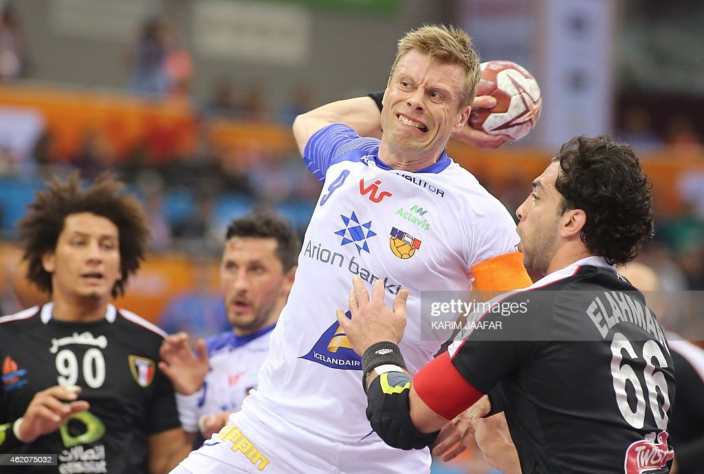 Iceland's Guojon Valur Sigurdsson (C) shoots the ball past Egypt's Ahmed El Ahmar during the 24th Men's Handball World Championships preliminary round Group C match between Egypt and Iceland at the Ali Bin Hamad al-Attiya Arena in Doha on January 24, 2015. AFP PHOTO / AL-WATAM DOHA / KARIM JAAFAR OUT==