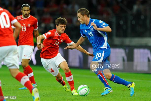 Iceland's Gylfi Sigurdsson vies with Switzeland's Valentin Stocker during the FIFA World Cup 2014 qualifying football match between Switzerland and...