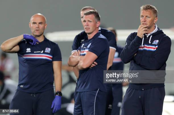 Iceland's head coach Heimir Hallgrimsson looks on with other memebers of the team from the sidelines during the friendly football match between...