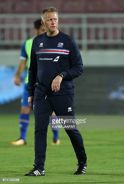 Iceland's head coach Heimir Hallgrimssson walks on the pitch as his team warms up prior to the start of the friendly football match between Iceland...