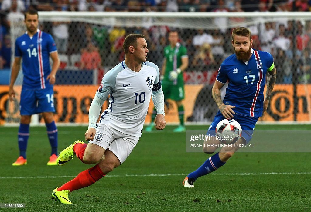 Iceland's midfielder Aron Gunnarsson (R) and England's forward Wayne Rooney vie for the ball during Euro 2016 round of 16 football match between England and Iceland at the Allianz Riviera stadium in Nice on June 27, 2016. / AFP / ANNE