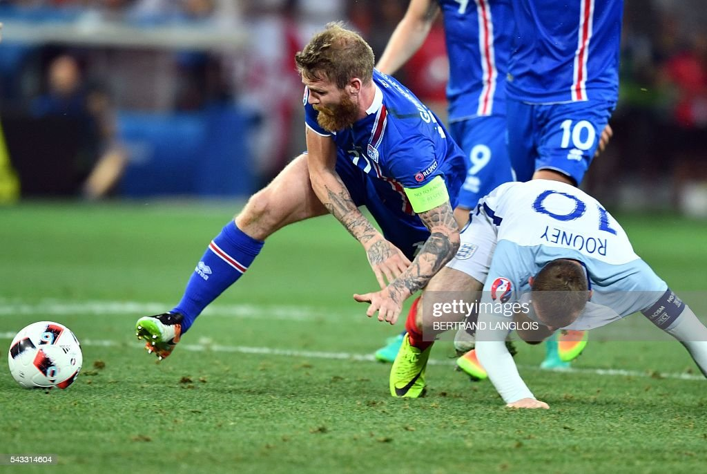 Iceland's midfielder Aron Gunnarsson and England's forward Wayne Rooney vie for the ball during the Euro 2016 round of 16 football match between England and Iceland at the Allianz Riviera stadium in Nice on June 27, 2016. / AFP / BERTRAND