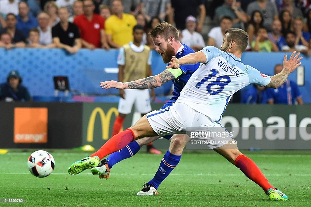 Iceland's midfielder Aron Gunnarsson and England's midfielder Jack Wilshere (front) vie for the ball during the Euro 2016 round of 16 football match between England and Iceland at the Allianz Riviera stadium in Nice on June 27, 2016. / AFP / BERTRAND