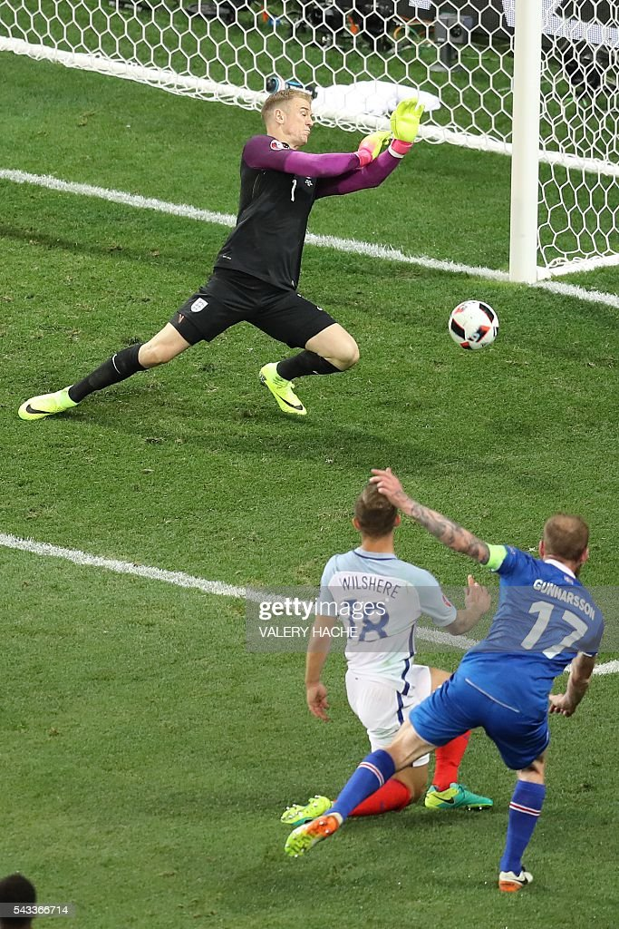 Iceland's midfielder Aron Gunnarsson (R) tries to score past England's midfielder Jack Wilshere and England's goalkeeper Joe Hart (L) during the Euro 2016 round of 16 football match between England and Iceland at the Allianz Riviera stadium in Nice on June 27, 2016. / AFP / Valery HACHE