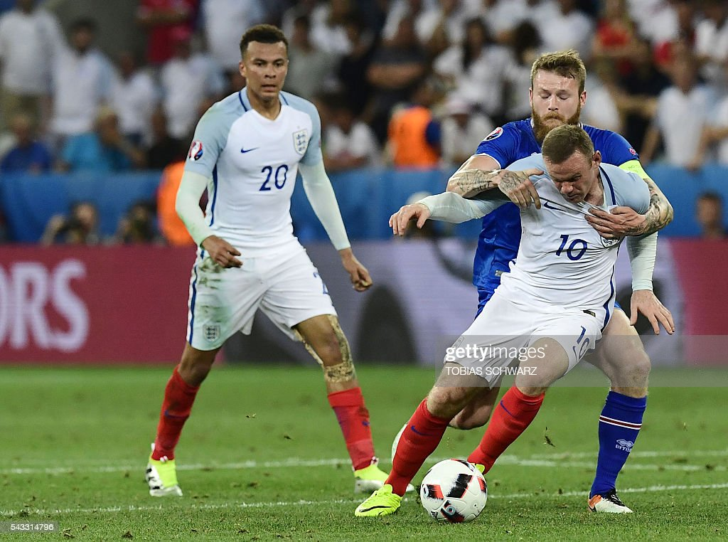 Iceland's midfielder Aron Gunnarsson (back) vies for the ball against England's forward Wayne Rooney as England's midfielder Dele Alli (L) looks on during Euro 2016 round of 16 football match between England and Iceland at the Allianz Riviera stadium in Nice on June 27, 2016. / AFP / TOBIAS