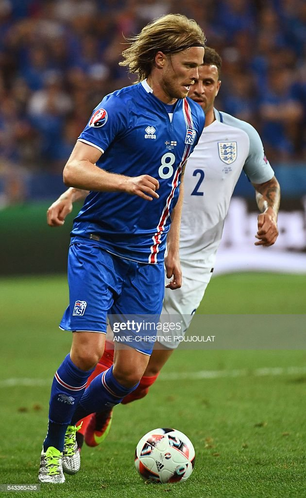 Iceland's midfielder Birkir Bjarnason (L) and England's defender Kyle Walker vie for the ball during Euro 2016 round of 16 football match between England and Iceland at the Allianz Riviera stadium in Nice on June 27, 2016. / AFP / ANNE