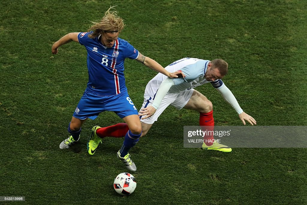 Iceland's midfielder Birkir Bjarnason (L) and England's forward Wayne Rooney vie for the ball during the Euro 2016 round of 16 football match between England and Iceland at the Allianz Riviera stadium in Nice on June 27, 2016. / AFP / Valery HACHE