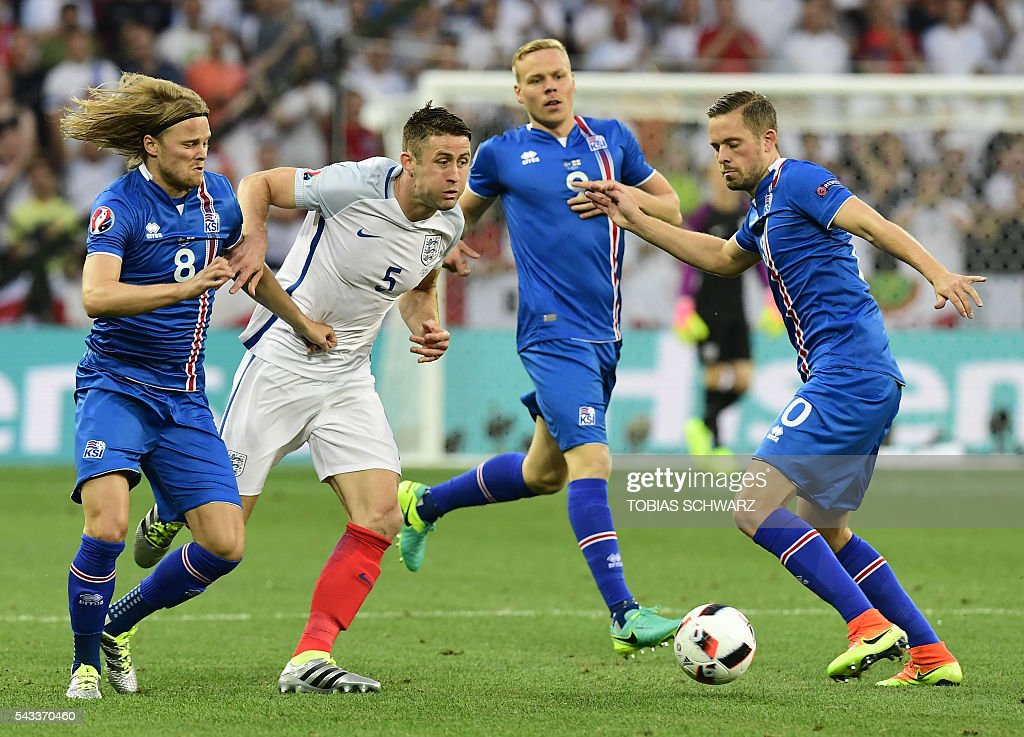 Iceland's midfielder Birkir Bjarnason (L) and Iceland's midfielder Gylfi Sigurdsson vie for the ball against England's defender Gary Cahill (2nd L) during Euro 2016 round of 16 football match between England and Iceland at the Allianz Riviera stadium in Nice on June 27, 2016. / AFP / TOBIAS