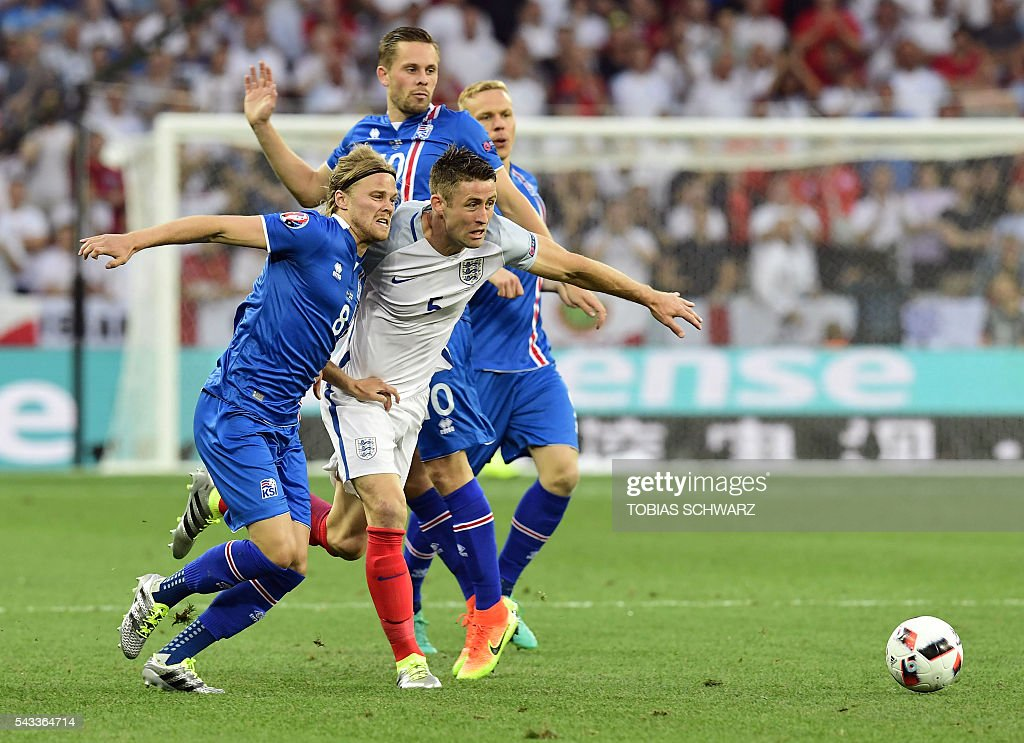 Iceland's midfielder Birkir Bjarnason (L) vies for the ball against England's defender Gary Cahill (C) during Euro 2016 round of 16 football match between England and Iceland at the Allianz Riviera stadium in Nice on June 27, 2016. / AFP / TOBIAS
