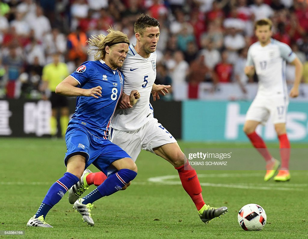 Iceland's midfielder Birkir Bjarnason (L) vies for the ball against England's defender Gary Cahill during Euro 2016 round of 16 football match between England and Iceland at the Allianz Riviera stadium in Nice on June 27, 2016. / AFP / TOBIAS
