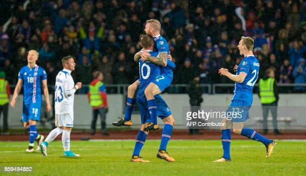 Iceland's midfielder Gylfi Sigurdsson and Iceland's midfielder Aron Gunnarsson celebate at the FIFA World Cup 2018 qualification football match...