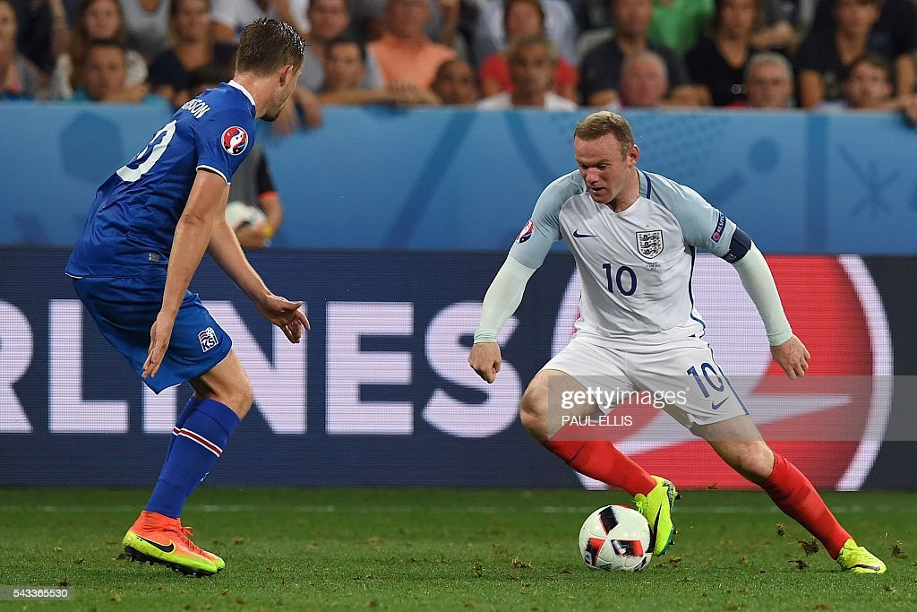 Iceland's midfielder Gylfi Sigurdsson eyes the ball played by England's forward Wayne Rooney during Euro 2016 round of 16 football match between England and Iceland at the Allianz Riviera stadium in Nice on June 27, 2016. / AFP / PAUL