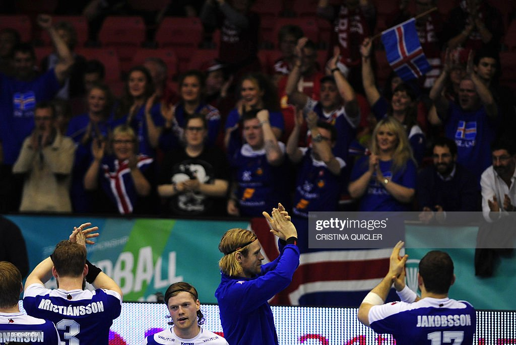 Iceland's players celebrate after winning during the 23rd Men's Handball World Championships preliminary round Group B match Iceland vs Qatar at the Palacio de Deportes San Pablo in Sevilla on January 18, 2013. Iceland won 39-29.AFP PHOTO/ CRISTINA QUICLER