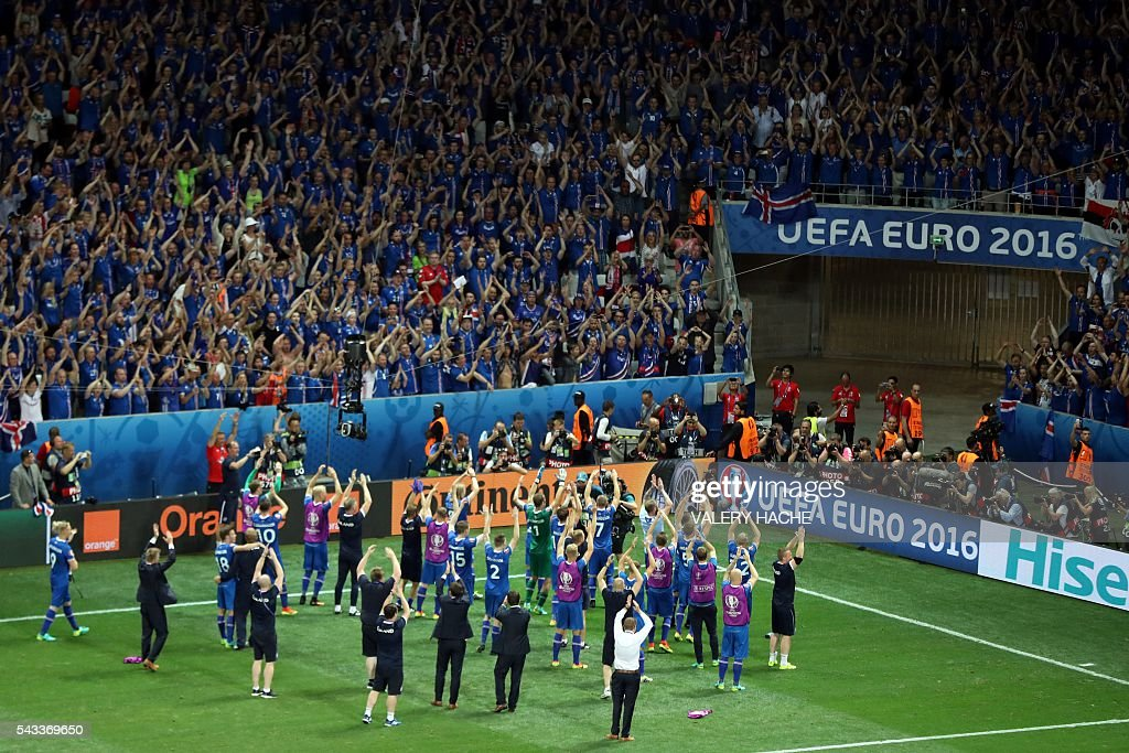 Iceland's players celebrate their team's win with supporters after the Euro 2016 round of 16 football match between England and Iceland at the Allianz Riviera stadium in Nice on June 27, 2016. Iceland won the match 1-2. / AFP / Valery HACHE