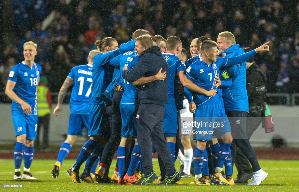 Iceland's players including Iceland's forward Johann Berg Gudmundsson (2nd R) celebrate after the FIFA World Cup 2018 qualification football match between Iceland and Kosovo in Reykjavik, Iceland on October 9, 2017. Iceland qualified for the FIFA World Cup 2018 as smallest country ever after beating Kosovo 2-0 at home in Reykjavik. / AFP PHOTO / Haraldur Gudjonsson