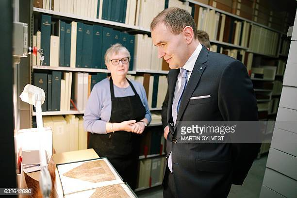 Iceland's President Gudni Johannesson looks at historic documents as he visits the collection of Arnamagnaean Manuscript items at the University of...