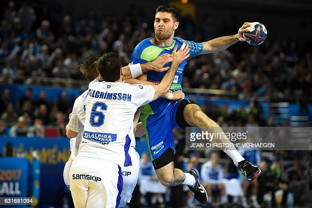 Iceland's right back Asgeir Orn Hallgrimsson blocks Slovenia's wing Blaz Janc vduring the 25th IHF Men's World Championship 2017 Group B handball...