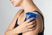 Shot of a young woman holding an icepack on her shoulder to ease the pain.