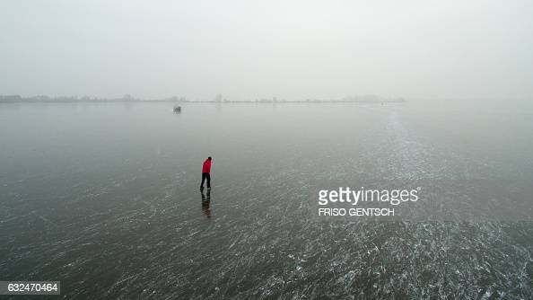 TOPSHOT A iceskater skates on the ice surface of the Duemmer lake near Damme northern Germany on January 23 2017 / AFP / dpa / Friso Gentsch /...