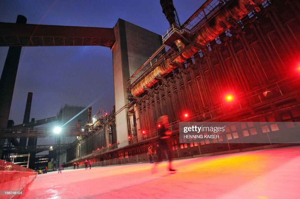 Ice-skaters glide on an outdoor rink at the former Zeche Zollverein coal mining plant in Essen, western Germany, on December 11, 2012. Mining activities at Zeche Zollverein started in 1851 and were closed down in 1986. Since 2001, the former industrial site is inscribed at the UNESCO World Heritage Sites list.