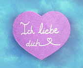 """Ich liebe dich"" text in german on Pink Heart and textured turquoise background"