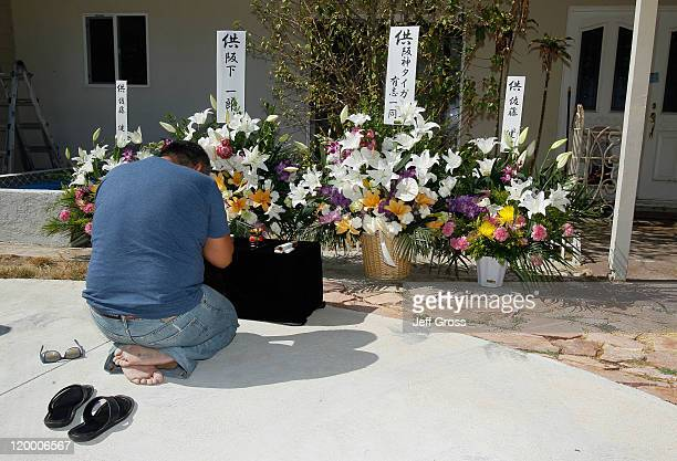Ichiro Sakashita prays next to flower bouquets left on behalf of the Japanese Hanshin Tigers baseball team outside the home where former Major League...