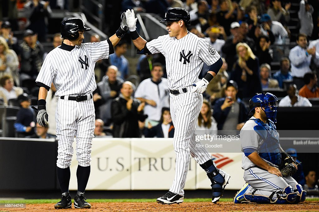 Ichiro Suzuki and Jacoby Ellsbury of the New York Yankees high five after scoring in the third inning against the Toronto Blue Jays at Yankee Stadium...