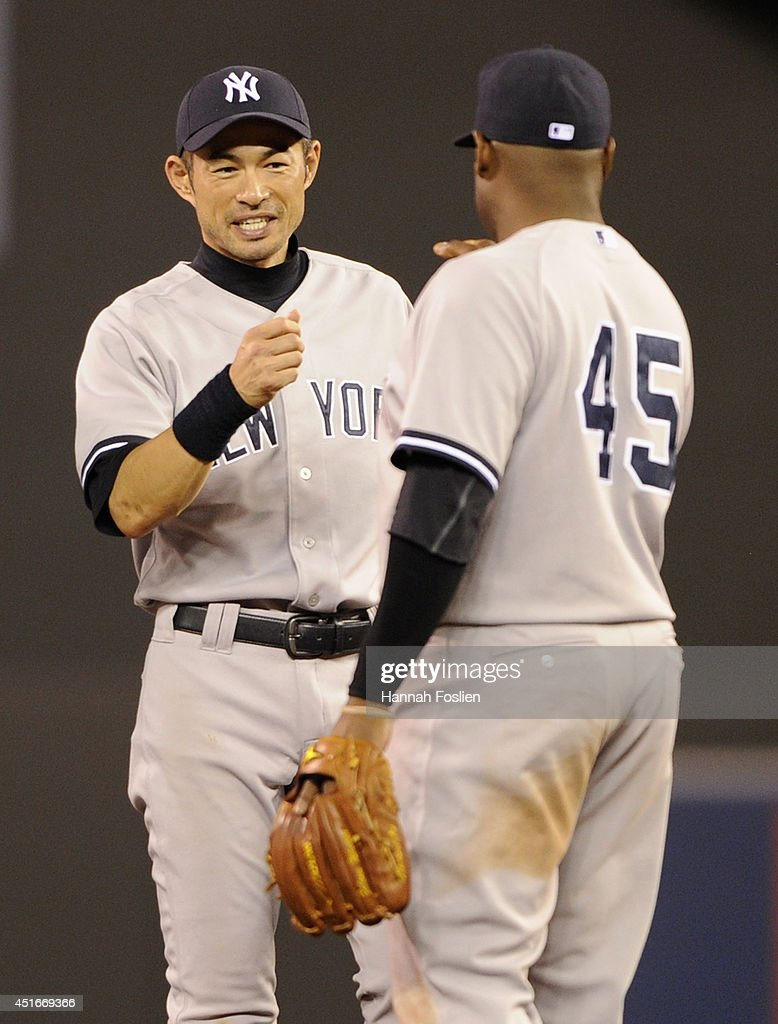 Ichiro Suzuki #31 and Zelous Wheeler #45 of the New York Yankees celebrate a win of the game against the Minnesota Twins on July 3, 2014 at Target Field in Minneapolis, Minnesota. The Yankees defeated the Twins 7-4.