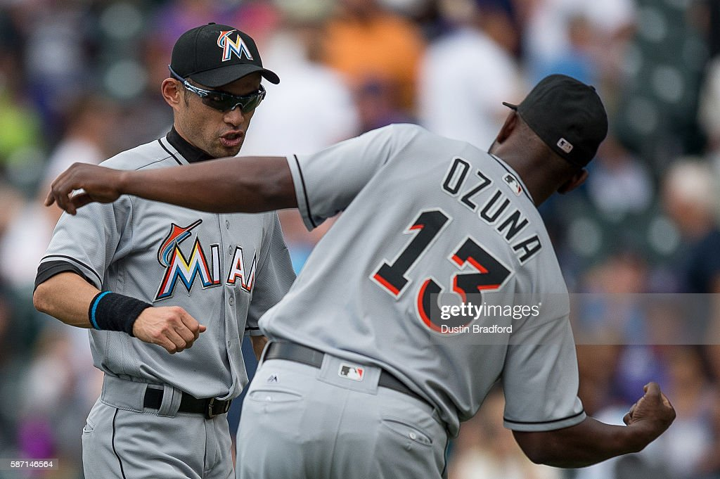 Ichiro Suzuki #51 andMarcell Ozuna #13 of the Miami Marlins celebrate a 10-7 win over the Colorado Rockies and the 3,000th major league hit of Suzuki earlier in the game, after a game at Coors Field on August 7, 2016 in Denver, Colorado.