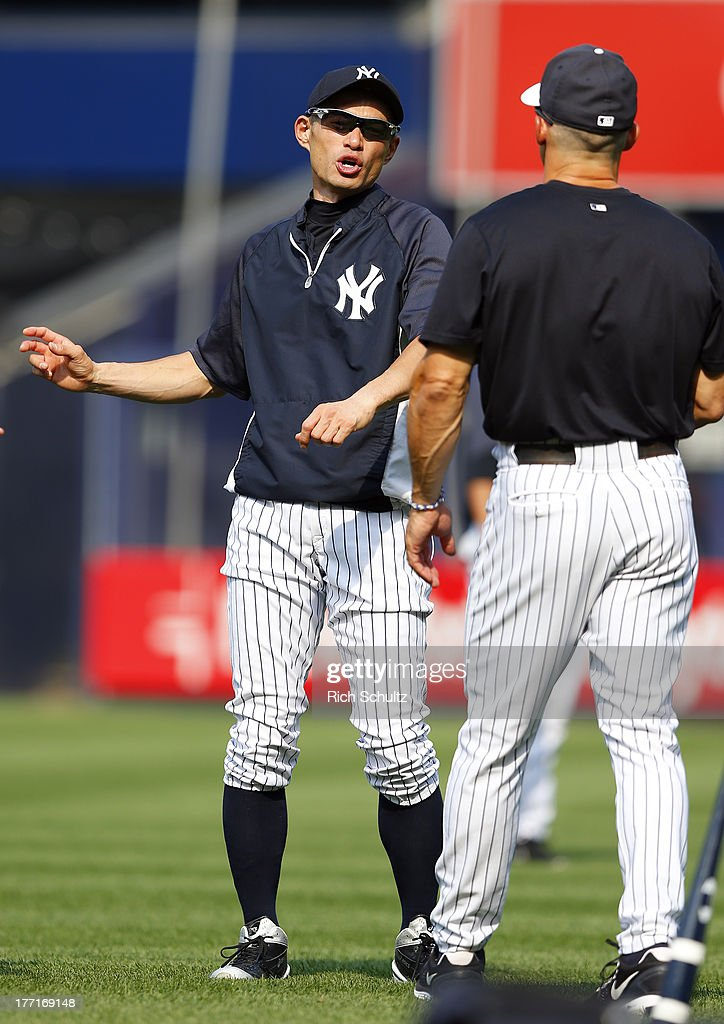 Ichiro Suzuki #31, left, talks with manager Joe Girardi #28 of the New York Yankees as he stretches before batting practice prior to the start of a game against the Toronto Blue Jays at Yankee Stadium on August 21, 2013 in the Bronx borough of New York City. Suzuki will be trying to get his 4000th career hit tonight.