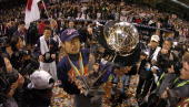 Ichiro Suzuki of Japan holds the World Baseball Classic Trophy as he is surrounded by a media throng after Japan defeated Cuba in the Championship...