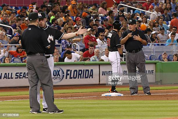 Ichiro Suzuki of the Miami Marlins and manager Mike Redmond both talk with umpires after Ichiro was called out at second base during the second...