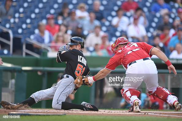 Ichiro Suzuki of the Miami Marlins beats the tag by Wilson Ramos of the Washington Nationals on a Christain Yelch single in the first inning during a...