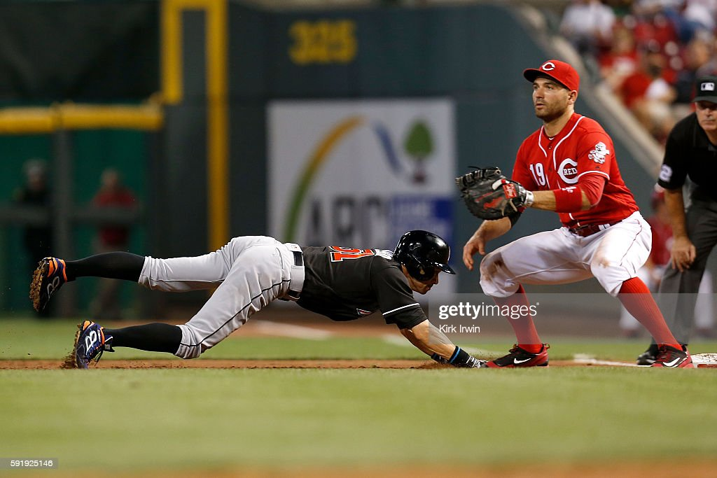 Ichiro Suzuki of the Miami Marlins beats the throw to Joey Votto of the Cincinnati Reds to safely make it back to first base during the sixth inning...